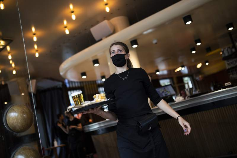 In this Wednesday, June 10, 2020 photo, a waitress, wearing a mouth mask to protect against the spread of coronavirus, works at the Bar du Matin restaurant in Brussels. (AP Photo/Francisco Seco)