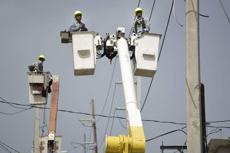 FILE - In this Oct. 19, 2017 file photo, Puerto Rico Electric Power Authority workers repair distribution lines damaged by Hurricane Maria in the Cantera community of San Juan, Puerto Rico. Private company Luma Energy took over the transmission and distribution operations of Puerto Ricos power authority on Tuesday, June 1, 2021. (AP Photo/Carlos Giusti, File)