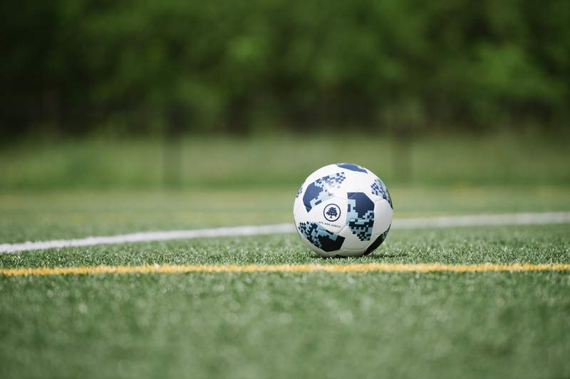 An AFC Ann Arbor ball rests on the pitch.