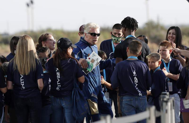 Virgin Galactic founder Richard Branson is greeted by school children before heading to board the rocket plane that will fly him to the edge of space from Spaceport America near Truth or Consequences, New Mexico, Sunday, July 11, 2021. (AP Photo/Andres Leighton)  - OJLRMGJO7VEC5B5MDY3LQNRHRM - Virgin Galactic launches spacecraft with Richard Branson into space