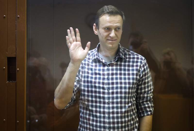 Russian opposition leader Alexei Navalny stands in a cage in the Babuskinsky District Court in Moscow, Russia, Saturday, Feb. 20, 2021. A Moscow court on Saturday considered Navalny's appeal against his prison sentence as the country faced a top European rights court's order to free the most prominent Kremlin foe. (AP Photo/Alexander Zemlianichenko)