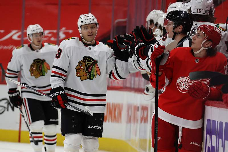 DETROIT, MICHIGAN - FEBRUARY 17: Philipp Kurashev #23 of the Chicago Blackhawks celebrates his second period goal with teammates while playing the Detroit Red Wings at Little Caesars Arena on February 17, 2021 in Detroit, Michigan. (Photo by Gregory Shamus/Getty Images)