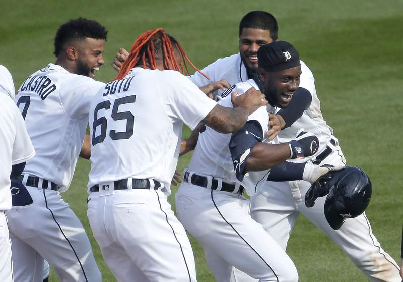Akil Baddoo #60 of the Detroit Tigers, right, celebrates with Willi Castro #9, Gregory Soto #65 and Jeimer Candelario #46 after hitting a single to drive in Harold Castro and defeat the Minnesota Twins 4-3 in 10 innings at Comerica Park on April 6, 2021, in Detroit, Michigan.