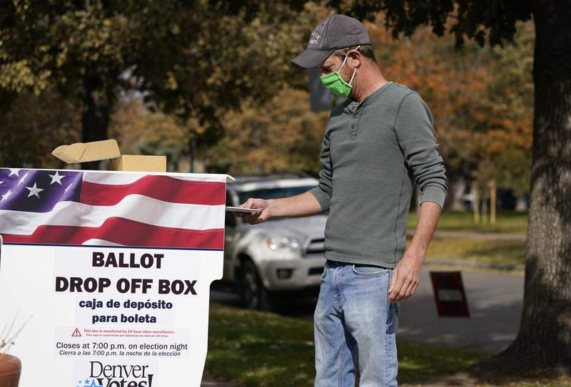 A voter wears a face covering as he place a ballot in a drop box outside the La Familia Recreation Center in the Baker neighborhood Tuesday, Nov. 3, 2020, south of downtown Denver. (AP Photo/David Zalubowski)