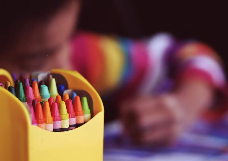 A child colors with crayons.