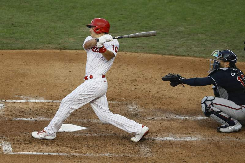 FILE - Philadelphia Phillies' J.T. Realmuto follows through after hitting a two-run home run off Atlanta Braves pitcher Robbie Erlin during the fourth inning of a baseball game in Philadelphia, in this Monday, Aug. 10, 2020, file photo. The Philadelphia Phillies and two-time All-Star catcher J.T. Realmuto agreed on a $115.5 million, five-year contract, two people familiar with the deal told The Associated Press. Both people spoke to The Associated Press on condition of anonymity Tuesday, Jan. 26, 2021, because Realmutos deal was pending a successful physical.(AP Photo/Matt Slocum, File)