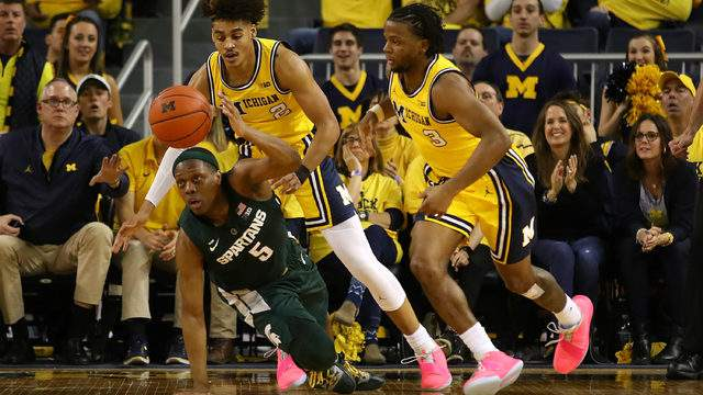 Cassius Winston tries to split the defense of Zavier Simpson and Jordan Poole at the Crisler Center on Feb. 24, 2019, in Ann Arbor. (Gregory Shamus/Getty Images)