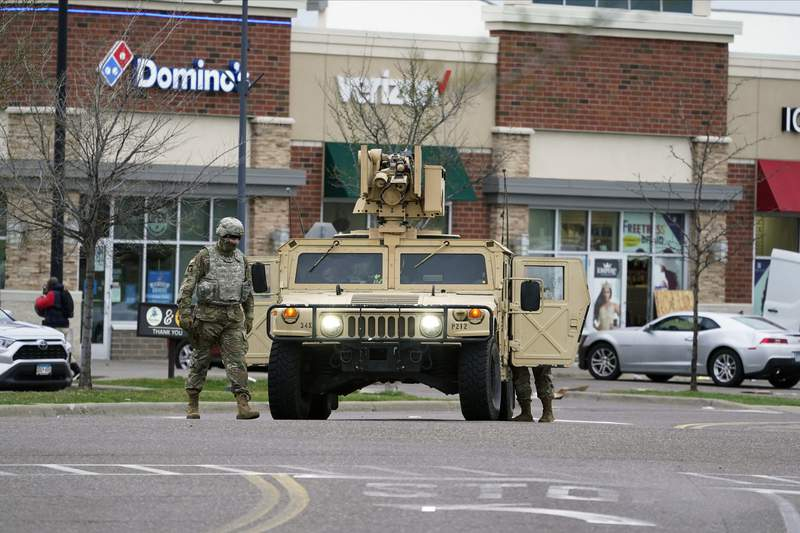 A National Guard soldier maintain watch and directs traffic at a shopping center in Brooklyn Center, Minn., a suburb of Minneapolis, Monday, April 12, 2021. A Black man died after being shot by police in a Minneapolis suburb during a traffic stop and crashing his car several blocks away, sparking violent protests that lasted into the early hours Monday as officers in riot gear clashed with demonstrators and the mans mother called for calm. (AP Photo/Jim Mone)