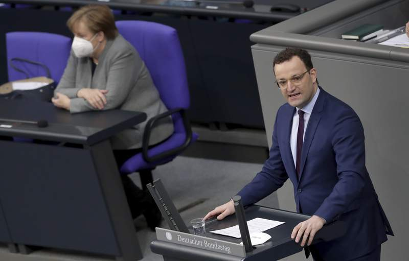 German Health Minister Jens Spahn delivers a speech during a meeting of the German federal parliament, Bundestag, at the Reichstag building in Berlin, Germany, Wednesday, Jan. 13, 2021 on the current developments of the new coronavirus pandemic in Germany. At left is German Chancellor Angela Merkel. (AP Photo/Michael Sohn)