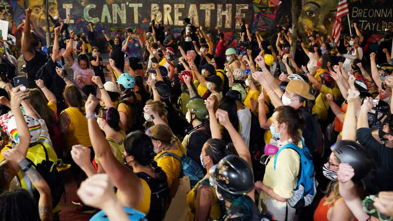 Protesters hold their fists in the air while marching past a mural with George Floyds last words during a march to the Mark O. Hatfield U.S. Courthouse on July 20, 2020 in Portland, Oregon. Monday night marked 54 days of protests in Portland following the death of George Floyd in police custody. (Photo by Nathan Howard)