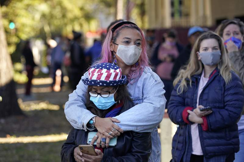 Erin Doherty hugs her mother Susanna Dew, 61, who is voting for the first time in her life, as they wait in line at a polling place on election day in the Mid City section of New Orleans, Tuesday, Nov. 3, 2020. (AP Photo/Gerald Herbert)