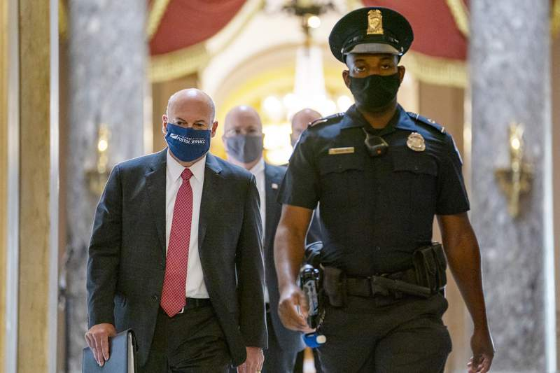 FILE - In this Aug. 5, 2020, file photo Postmaster General Louis DeJoy, left, is escorted to House Speaker Nancy Pelosi's office on Capitol Hill in Washington. The U.S. Postal Service has sent letters to 46 states and the District of Columbia, warning it cannot guarantee all ballots cast by mail for the November election will arrive in time to be counted, The Washington Post reported Friday, Aug. 14. DeJoy, a former supply-chain CEO and a major donor to President Donald Trump and other Republicans, has pushed cost-cutting measures to eliminate overtime pay and hold mail until the next day if postal distribution centers are running late. (AP Photo/Carolyn Kaster, File)