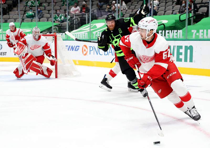 DALLAS, TEXAS - JANUARY 28:  Taro Hirose #67 of the Detroit Red Wings skates the puck against the Dallas Stars in the second period at American Airlines Center on January 28, 2021 in Dallas, Texas. (Photo by Ronald Martinez/Getty Images)