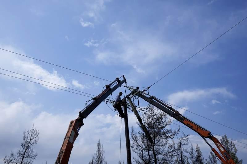 A worker is seen fixing an electricity power line near village Milies on Evia island, Thursday, Aug. 12, 2021. (AP Photo/Petros Karadjias)