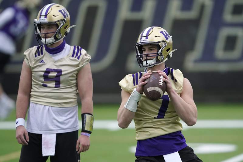 FILE - Washington quarterback Sam Huard, right, drops to pass next to quarterback Dylan Morris, left, during the first day of NCAA college football practice in Seattle, in this Wednesday, April 7, 2021, file photo. The NCAA football oversight committee is preparing to recommend changes to preseason camp that will include fewer fully padded practices and the elimination of some old-school collision drills. The football oversight committee 's initial proposal called for at least nine of a team's 25 preseason practices to be run with players wearing helmets but no other pads, and no more than eight fully-padded, full-contact practices. (AP Photo/Ted S. Warren, File)
