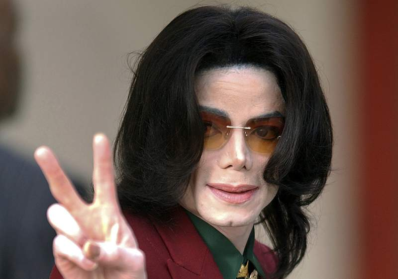 FILE - In this Thursday, March 17, 2005, file photo, pop star Michael Jackson acknowledges his fans as he arrives at the Santa Barbara County Courthouse, in Santa Maria, Calif. The Michael Jackson estate is donating $300,000 to help people in the entertainment industry hurt by the coronavirus pandemic. The donations will focus on Broadway workers, as well as workers in Las Vegas and in the music industry, Jackson's estate announced Wednesday, March 25, 2020. (AP Photo/Michael A. Mariant, File)