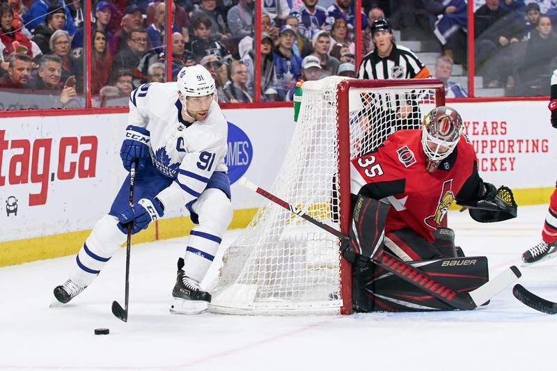 OTTAWA, ON - FEBRUARY 15:  John Tavares #91 of the Toronto Maple Leafs skates around the net with the puck as Marcus Hogberg #35 of the Ottawa Senators defends the net at Canadian Tire Centre on February 15, 2020 in Ottawa, Ontario, Canada.  (Photo by Jana Chytilova/Freestyle Photography/Getty Images)