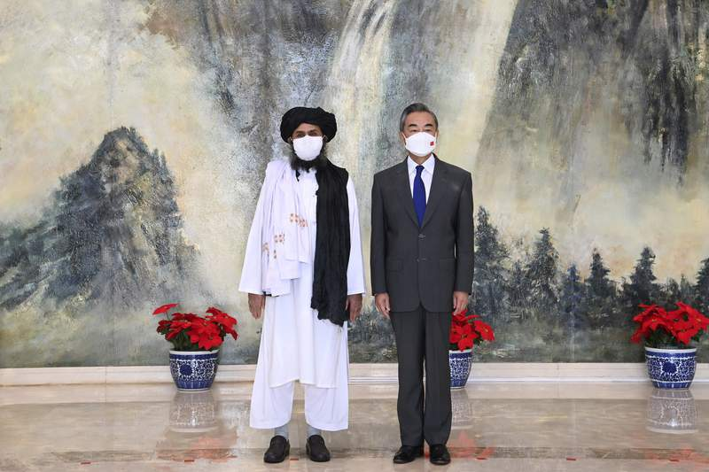 In this photo released by China's Xinhua News Agency, Taliban co-founder Mullah Abdul Ghani Baradar, left, and Chinese Foreign Minister Wang Yi pose for a photo during their meeting in Tianjin, China, Wednesday, July 28, 2021. Wang met with a delegation of high-level Taliban officials as ties between them warm ahead of the U.S. pullout from Afghanistan. (Li Ran/Xinhua via AP)