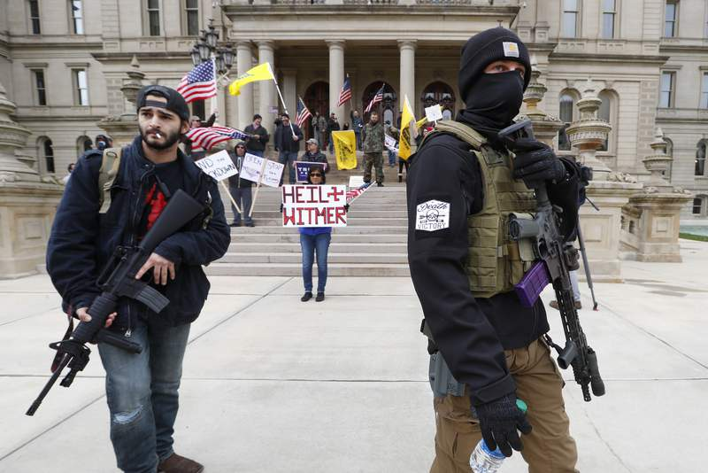 FILE - In this April 15, 2020, file photo, men carry rifles near the steps of the State Capitol building in Lansing, Mich., during a protest over Michigan Gov. Gretchen Whitmer's orders to keep people at home and businesses locked during the coronavirus outbreak.(AP Photo/Paul Sancya, File)