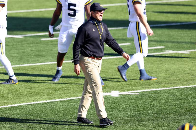 Head coach Jim Harbaugh of the Michigan Wolverines walks on the field calling out to his team during warm ups before the game against the Indiana Hoosiers at Memorial Stadium on November 07, 2020 in Bloomington, Indiana.