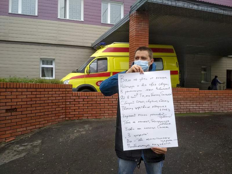 A man holding a placard stands in a one-person picket in front of a building of a hospital intensive care unit where Alexei Navalny was hospitalized in Omsk, Russia, Thursday, Aug. 20, 2020. Russian opposition politician Alexei Navalny is on a hospital ventilator in a coma, after falling ill from a suspected poisoning, according to his spokeswoman Kira Yarmysh. (AP Photo/Evgeniy Sofiychuk)