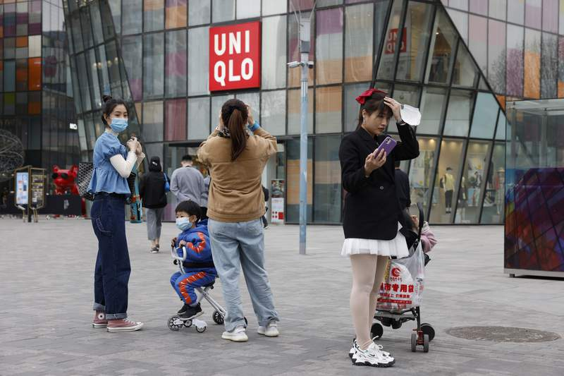 FILE - In this Monday, March 29, 2021 file photo, visitors to a shopping mall wearing masks stand before a Uniqlo store in Beijing. French prosecutors have on Friday, July 2 opened an investigation into alleged involvement in crimes against humanity based on accusations that global retailers, including Uniqlo and the makers of Skechers shoes and Zara clothes, rely on forced labor of minorities in China. (AP Photo/Ng Han Guan)