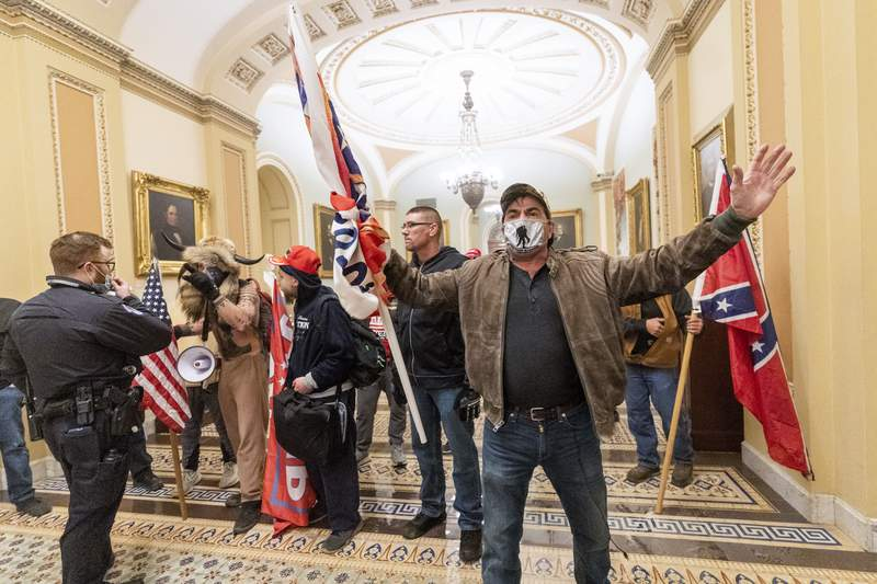 FILE - In this Jan. 6, 2021, file photo, supporters of President Donald Trump are confronted by U.S. Capitol Police officers outside the Senate Chamber inside the Capitol in Washington. Both within and outside the walls of the Capitol, banners and symbols of white supremacy and anti-government extremism were displayed as an insurrectionist mob swarmed the U.S. Capitol. (AP Photo/Manuel Balce Ceneta, File)