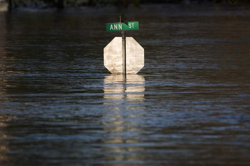 Floodwater reaches the bottom of a stop sign, Wednesday, May 20, 2020, in Midland, Mich. (Katy Kildee/Midland Daily News via AP)