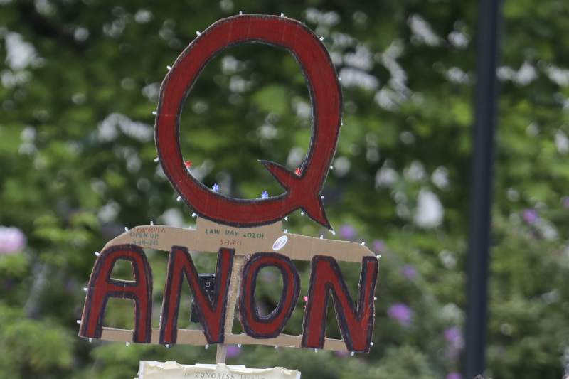 FILE - In this May 14, 2020, file photo, a person carries a sign supporting QAnon at a protest rally in Olympia, Wash. Facebook said Tuesday, Oct. 6, 2020, that it will remove Facebook pages, groups and Instagram accounts for representing QAnon. (AP Photo/Ted S. Warren, File)
