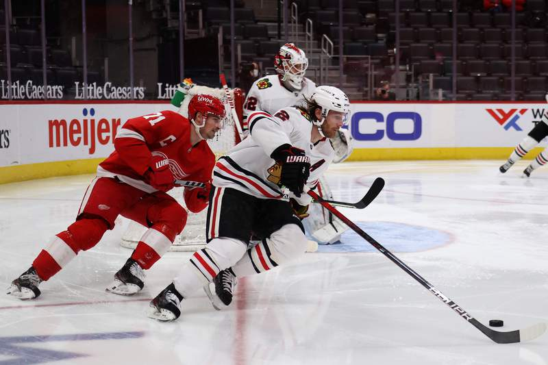 DETROIT, MICHIGAN - FEBRUARY 17: Duncan Keith #2 of the Chicago Blackhawks tries to stay in front of Dylan Larkin #71 of the Detroit Red Wings during the second period at Little Caesars Arena on February 17, 2021 in Detroit, Michigan. (Photo by Gregory Shamus/Getty Images)