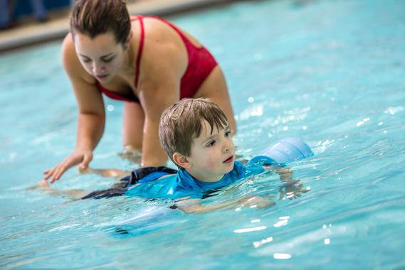A swim instructor teaches a young student in December 2015.
