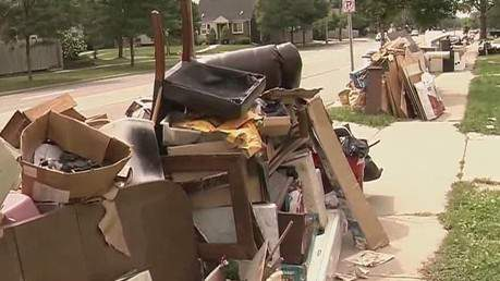 Debris clutters a street curb after a historic flooding in August 2014 in Royal Oak, Mich.