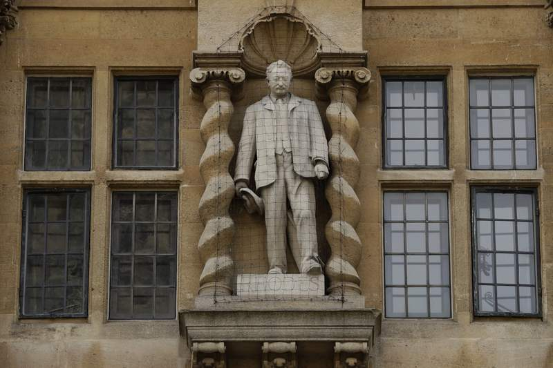FILE - In this Wednesday, June 17, 2020 file photo, a view of the statue of Cecil Rhodes, the Victorian imperialist who supported apartheid-style measures in southern Africa stands mounted on the facade of Oriel College in Oxford, England. The controversial statue of Victorian imperialist Cecil Rhodes will not be taken down because of regulatory and financial challenges, the governing body of Oxford Universitys Oriel College said Thursday, May 20, 2021. The decision follows a long-running campaign to remove the statue of a man who made a fortune in the late 19th century from gold and diamond mines where miners labored in brutal conditions.  (AP Photo/Matt Dunham, File)