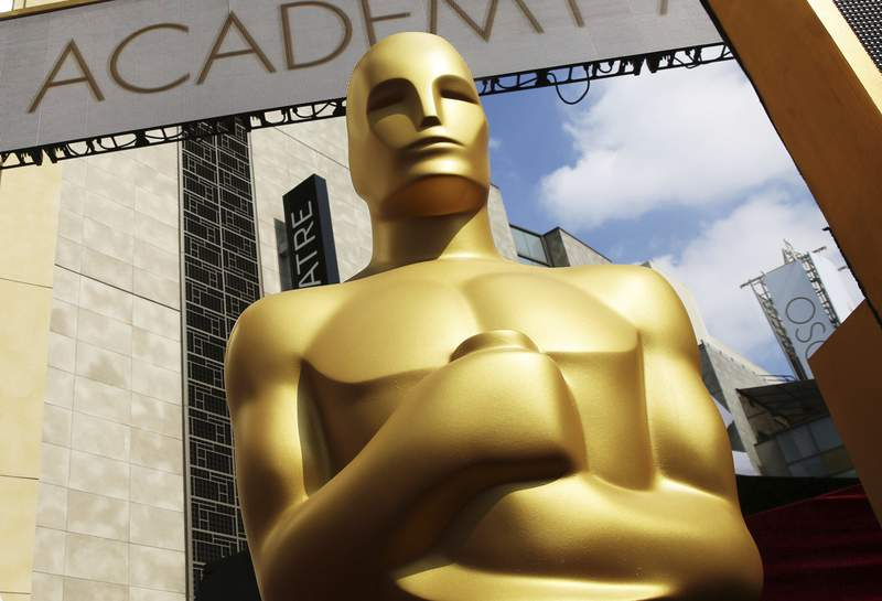 FILE - In this Feb. 21, 2015 file photo, an Oscar statue appears outside the Dolby Theatre for the 87th Academy Awards in Los Angeles. The theater has been the home of the Oscars since 2001 and the organizers say the upcoming show will keep that tradition, but they will enlist a supporting cast of venues. An academy spokesperson said Wednesday that the ceremony this year will be broadcast live from multiple locations on April 25. (Photo by Matt Sayles/Invision/AP, File)