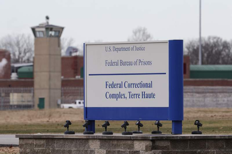 FILE - In this Dec. 10, 2019, file photo the guard tower flanks the sign at the entrance to the U.S. Penitentiary in Terre Haute, Ind. The Justice Department plans to resume federal executions next week for the first time in more than 15 years, despite the coronavirus pandemic raging both inside and outside prisons and stagnating national support for the death penalty. Three people are slated to die by lethal injection in one week beginning Monday. The executions will take place at USP Terre Haute. (AP Photo/Michael Conroy, File)