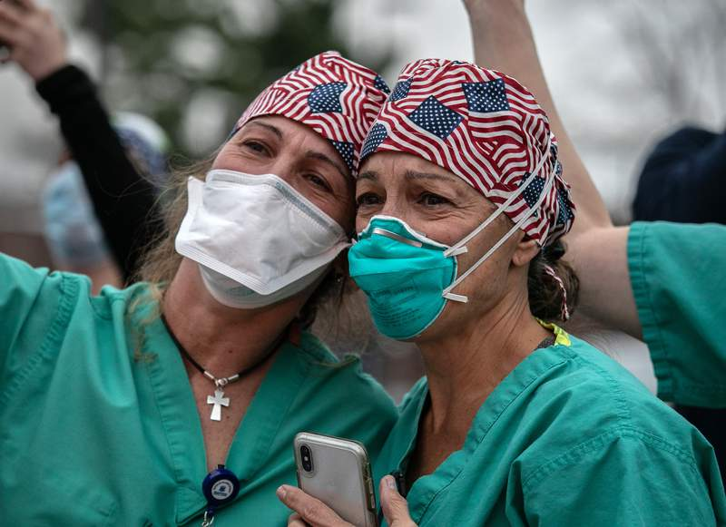 Hospital workers, including ER RN Adele Rushneck-Feeney, at right, watch outside the Westchester Medical Center as first responders pass by in a caravan of sirens and lights on April 14 in Valhalla, New York. The first responders arrived in EMS ambulances, fire department trucks and police vehicles to give thanks to health care workers for their efforts in combating the coronavirus pandemic in Westchester County, N.Y.