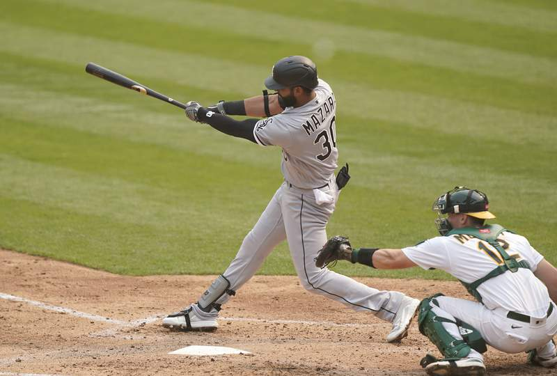 Nomar Mazara #30 of the Chicago White Sox hits an RBI double scoring Luis Robert #88 against the Oakland Athletics during the third inning of Game Three of the American League Wild Card Round at RingCentral Coliseum on October 01, 2020 in Oakland, California.