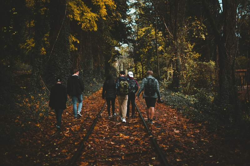 Young people walk in a group outside.