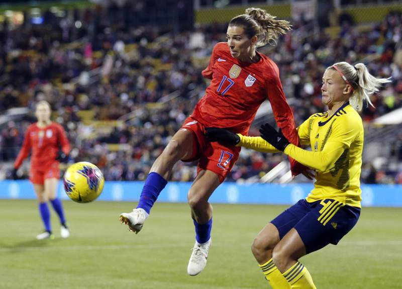 FILE - In this Thursday, Nov. 7, 2019 file photo, United States forward Tobin Heath, left, passes the ball in front of Sweden defender Hanna Glas during the first half of a women's international friendly soccer match in Columbus, Ohio. Tobin Heath will soon be hoping to play at Old Trafford again. The winger has more chance now she has signed for Manchester United, although the Womens Super League team has yet to play in the stadium that has been home to the mens side for 110 years. (AP Photo/Paul Vernon, File)