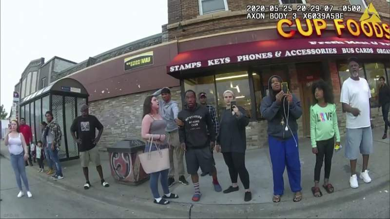 FILE - This May 25, 2020, file image from a police body camera shows bystanders including Darnella Frazier, third from right filming, as former Minneapolis police officer Derek Chauvin was recorded pressing his knee on George Floyd's neck for several minutes in Minneapolis. Frazier, the teenager who pulled out her cellphone and recorded the police restraint and death of Floyd has been awarded a special citation by the Pulitzer Prizes. The Pulitzer Prizes said Friday, June, 11, 2021, that Frazier was cited for courageously recording the video, which spurred protests against police brutality around the world. (Minneapolis Police Department via AP, File)