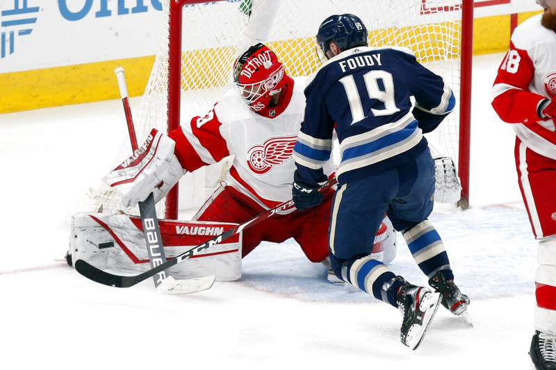 Detroit Red Wings goalie Thomas Greiss, left, stops a shot by Columbus Blue Jackets forward Liam Foudy during an NHL hockey game in Columbus, Ohio, Friday, May 7, 2021. The Red Wings won 5-2. (AP Photo/Paul Vernon)