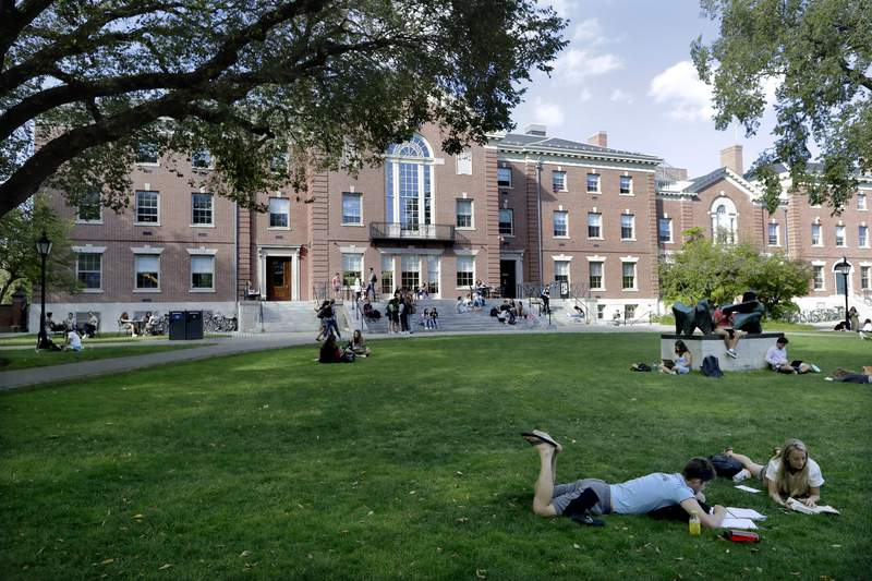 FILE - In this Sept. 25, 2019, file photo, people rest on grass while reading at Brown University in Providence, R.I. The university and attorneys for student-athletes, who challenged the Ivy League school's decision to reduce several women's varsity sports teams to club status, announced a proposed settlement Thursday, Sept. 17, 2020. (AP Photo/Steven Senne, File)