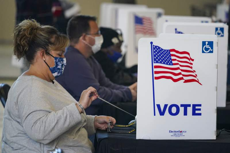 A voter begins to cast her ballot during voting at a poling place inside Bankers Life Fieldhouse in Indianapolis, on Election Day Tuesday, Nov. 3, 2020. (AP Photo/Michael Conroy)