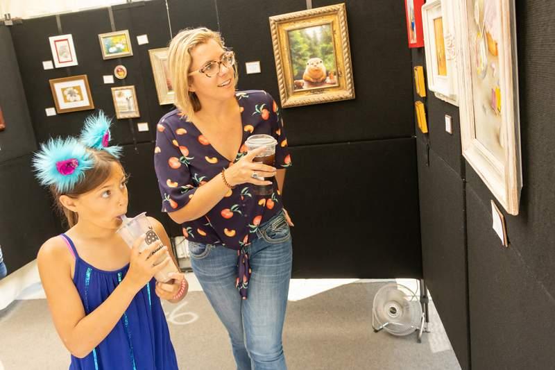 Fairgoers in an artist booth at the Ann Arbor Art Fair in July 2021.