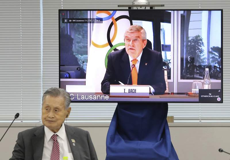 In this Sept. 24, 2020, file photo, IOC President Thomas Bach, on the screen, speaks remotely with Tokyo 2020 Organizing Committee President Yoshiro Mori, left, during an online meeting focused on how to pull off the delayed Tokyo Games, in Tokyo. Tokyo Olympic organizers estimate they have found saving of about $280 million by simplifying and cutting out some frills from next year's postponed Games. (Du Xiaoyi/Pool Photo via AP, File)