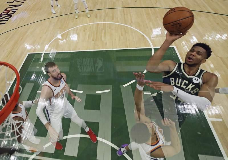 Milwaukee Bucks' Giannis Antetokounmpo (34) shoots over Phoenix Suns' Devin Booker in Game 3 of basketball's NBA Finals, Sunday, July 11, 2021, in Milwaukee. (Jonathan Daniel/Pool Photo via AP)
