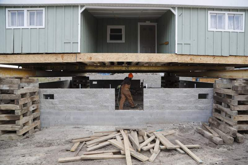 In this Wednesday, Jan. 8, 2020, photo, laborer Logan Farrington works under a house being lifted in Luna Pier, Mich. The project will protect the home from the potential rising lake levels of Lake Erie. High water is wreaking havoc across the Great Lakes, which are bursting at the seams less than a decade after bottoming out. The sharp turnabout is fueled by the region's wettest period in more than a century that scientists say is likely connected to the warming climate. (AP Photo/Carlos Osorio)