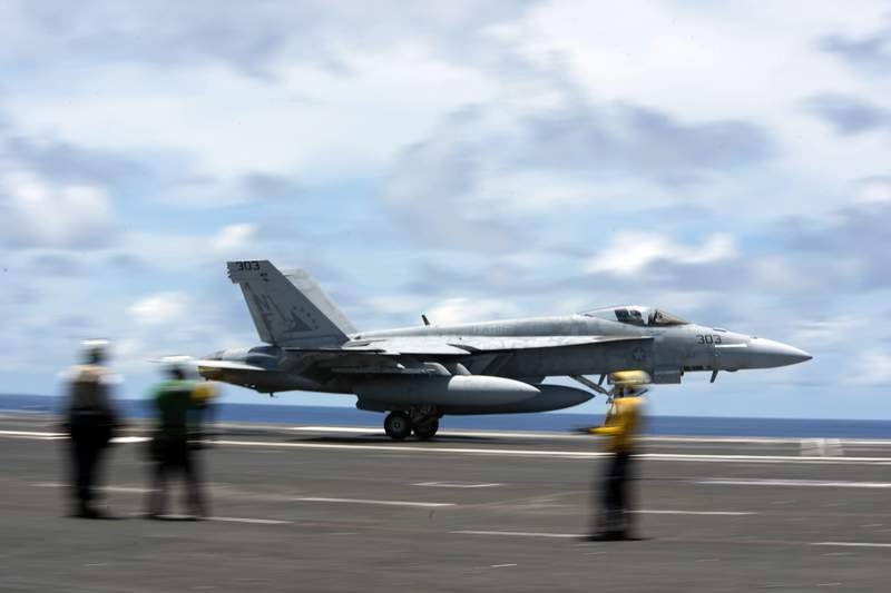 """200610-N-ML137-1057 PHILIPPINE SEA (June 10, 2020) In this image provided by the U.S. Navy, an F/A-18E Super Hornet attached to the """"Eagles"""" of Strike Fighter Squadron (VFA) 115 practices a touch-and-go maneuver on the flight deck of the Navy's only forward-deployed aircraft carrier USS Ronald Reagan (CVN 76) on June 10, 2020, in the Philippine Sea. (Mass Communication Specialist 2nd Class Samantha Jetzer/U.S. Navy via AP)"""