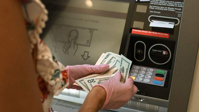 A person withdrawing money from an ATM.