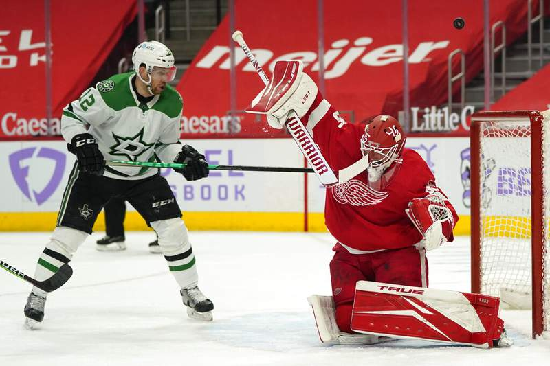 Detroit Red Wings goaltender Jonathan Bernier (45) deflects a shot as Dallas Stars center Radek Faksa (12) watches for a rebound in the first period of an NHL hockey game Saturday, April 24, 2021, in Detroit. (AP Photo/Paul Sancya)